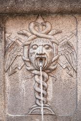 Close-up of an ancient fountain with a caduceus sculpture