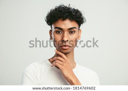 Close-up of an androgynous man with his hand on chin. Young guy with feminine facial features looking at camera against white background.