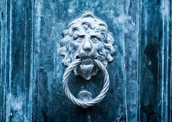 Close-up of an antique metal doorknob with a lion face on a wooden door. Old bronze traditional knocker. Concept for antique, gothic, mistery