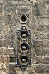 Close-up of an antique, rusty iron door bell on the exterior wall of an old brick building, Siena, Tuscany, Italy