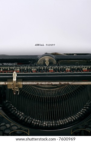 Close up of an antique typewriter with the words Annual report written on the paper - main focus on letters