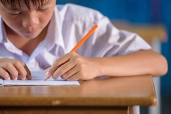 Close-up of an Asian male student in elementary school writing with her left hand. Concept: left-handed