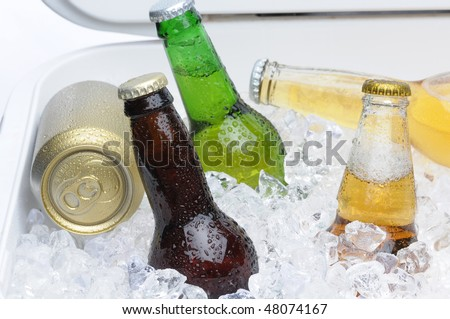 Close up of an assortment of beer bottles and cans in cooler with ice horizontal composition