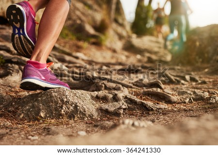 Close up of an athlete\'s feet wearing sports shoes on a challenging dirt track. Trail running workout on rocky terrain outdoors.