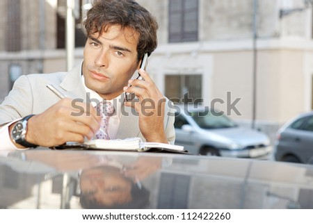 Close up of an attractive businessman using a cell phone and taking notes while leaning on a car in the city.