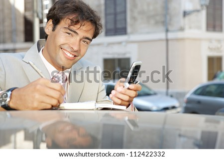 Close up of an attractive businessman using a cell phone and taking notes while leaning on a car in the city, smiling.