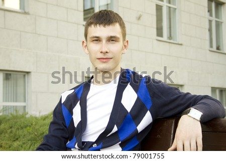 Close-up of an attractive male student sitting on a wooden bench in the campus