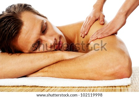 Close-up of an attractive man enjoying a back massage in a spa center