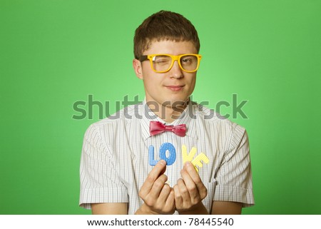 "Close-up of an attractive man in love with ""nerd"" in his hands four letters ""LOVE"" #78445540"