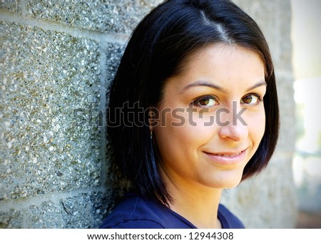 Close-up of an attractive young woman leaning against a concrete wall. Horizontally framed shot.