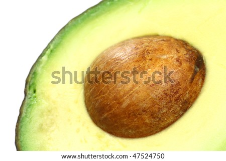 close up of an avocado half with seed on a white background