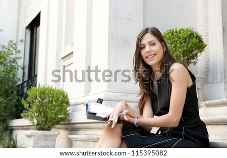 Close up of an elegant businesswoman sitting on a classic buildings steps taking notes in her agenda, smiling.