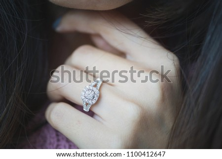 Close up of an elegant diamond ring on woman finger with dark pink sweater winter clothe background. soft and selective focus.love and wedding concept.