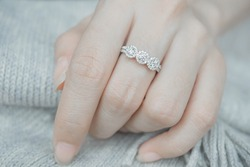 Close up of an elegant diamond ring on woman's finger. (soft and sellective focus)
