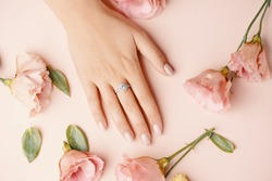 Close up of an elegant diamond ring on young woman finger. Woman hands with manicure and jewelry ring on pink background with flowers, beauty style concept.