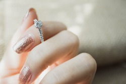 Close up of an elegant engagement diamond ring on woman finger. love and wedding concept. soft and selective focus.
