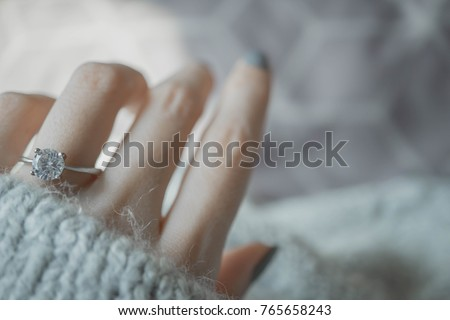 Close up of an elegant engagement diamond ring on woman finger with dark gray sweater winter clothe background. love and wedding concept. soft and selective focus.
