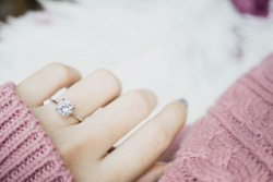 Close up of an elegant engagement diamond ring on woman finger with dark pink sweater winter clothe. love and wedding concept.