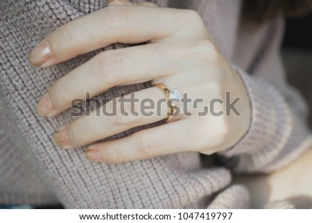 Close up of an elegant engagement diamond ring on woman finger with dark pink sweater winter clothe. love and wedding concept.soft and selective focus. #1047419797