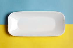 Close-up of an empty ceramic white rectangular or rectangle tray plate for mockup. Over yellow blue background