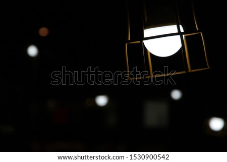 Close up of an Energy Saving Lightbulb With Guard Cage and Blurry Lightbulbs at the Back on a Night Background #1530900542
