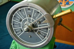 Close up of an engine order telegraph or E.O.T (or chadburn) on a Dutch ship with the dial indicating in text from Full Ahead (Volle Kracht) to Stop