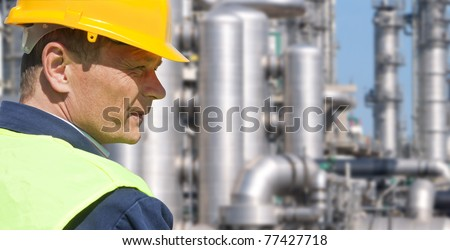 Close up of an engineer wearing a safety vest, blue coveralls, and a hard hat in front of a petrochemical plant - stock photo