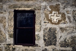 Close-up of an exterior stone wall of an old church with a window and cross, Bulgaria