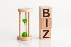 Close-up of an hourglass next to wooden blocks with the text BIZ. biz - text in wooden building blocks, white backgrounds.