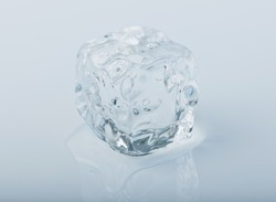 Close-up of an ice cube slowly melting away in a puddle of water