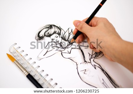 Close-up of an illustrator  hand drawing a fashion sketch #1206230725
