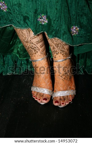 Close-up of an Indian bride's feet decorated with henna. - stock photo