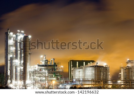 Close-up of an oil-refinery plant and a yellow night-sky