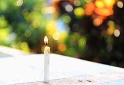 Close-up of an old candle on a wooden floor Colorful light as background selective focus and shallow depth of field