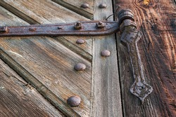 Close-up of an old, corroded and rusty hinge holding the wooden door. Details of wood and metal structure and soft focus.