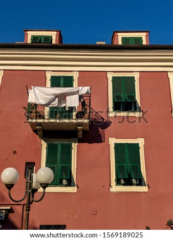 Close-up of an old exterior building with washing lines, green shutters and red colored fa?ade wall, Liguria, Italy Photo stock ©