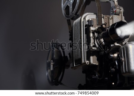 Close-up of an old film projector. Retro movie 16 mm on a dark background. Showing an old film in a movie theater