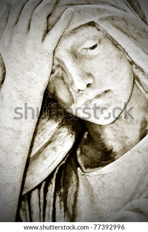 Close up of an old grunge statue representing a suffering young woman with a hand in her forehead