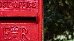 Close up of an old square style red post box in UK