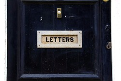 Close-up of an old vintage letterbox, London, England. Mail concept, letters, doorbell button.