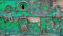 Close up of an old wooden crate painted green with a rusty lock