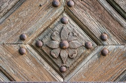 Close-up of an old wooden door decorated with carved wood made flowers with corroded and rusty fittings.