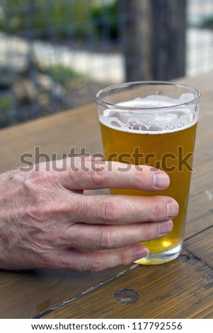 Close up of an older man\'s hand holding a glass of beer on a picnic table.