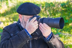 Close-up of an older man taking a picture in nature. Concept of enjoying in nature