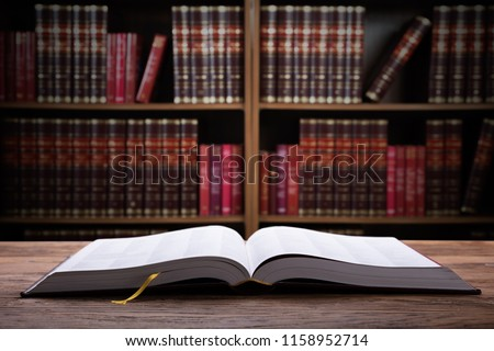 Close-up Of An Open Law Book On Wooden Desk In Courtroom #1158952714