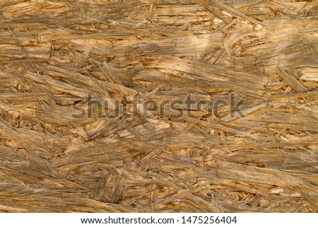 Close-up of an oriented strand board (OSB) texture with compressing layers of wood strands