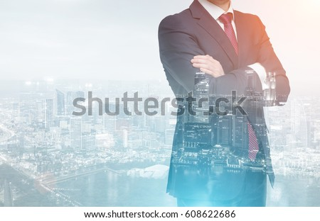 Close up of an unrecognizable businessman standing with his arms crossed against a city panorama. Double exposure. Toned image #608622686