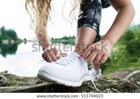 Close up of an unrecognizable young runner tying shoelaces #551744023