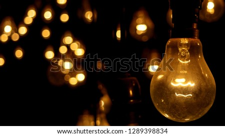 Close up of an vintage incandescent light bulb against dark background with unfocused lights.