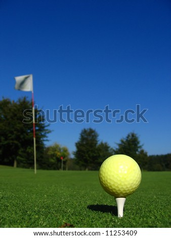 Close up of an yellow golf ball on the tee nearby the hole
